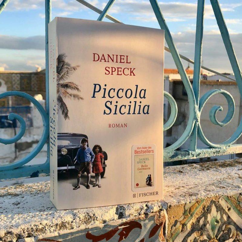 Das Buch Piccola Sicilia von Daniel Speck lehnt auf einem Mäuerchen an einem türkisfarben gestrichenen Eisengitter. Im Hintergrund ist die Stadt Tunis zu sehen.