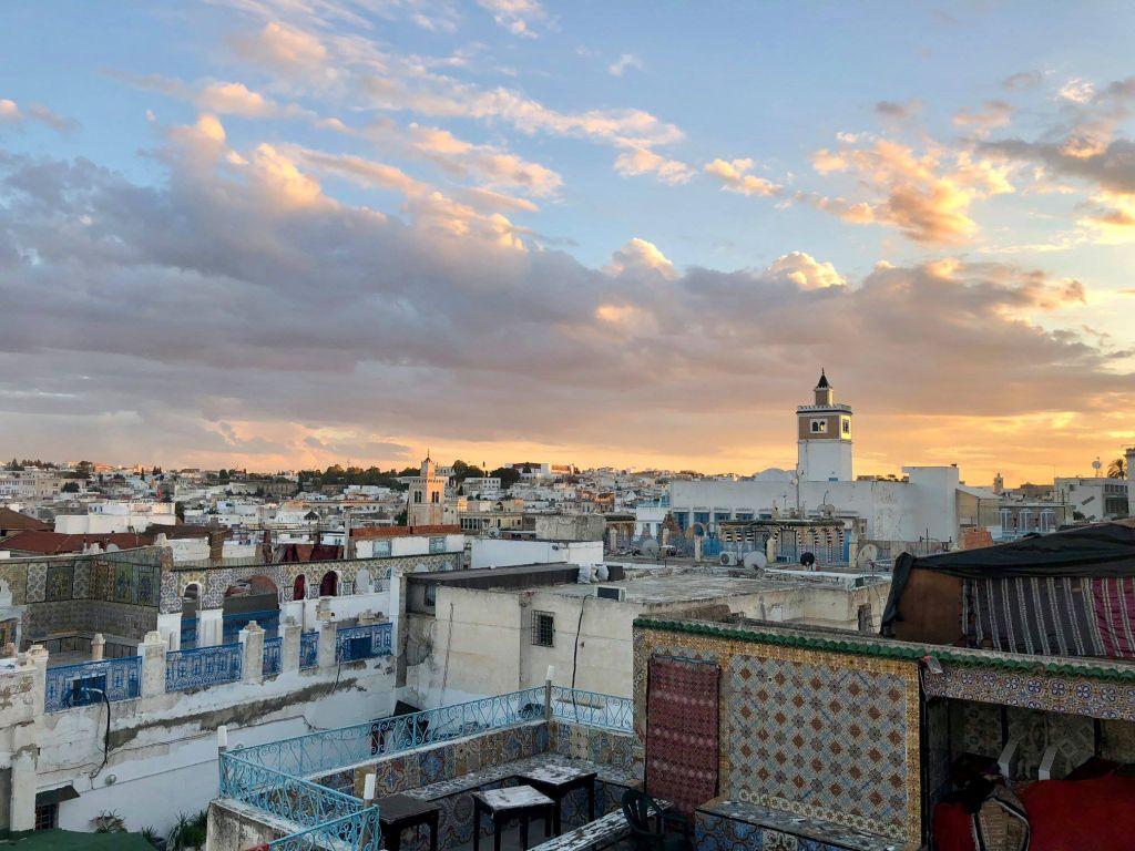 Die Stadt Tunis ist in ein warmes weiches Licht getaucht. Man blickt auf ihre Dächer und Dachterrassen. Positive Farben und Muster unterstreichen die eindrucksvolle Kulisse.