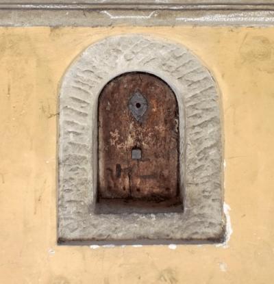 Das gut erhaltene Weinfenster in der Via Torta. An der gelben Mauer, mit Stein umrandet und mit einem gut erhaltenen, braunen Holztürchen versehen.