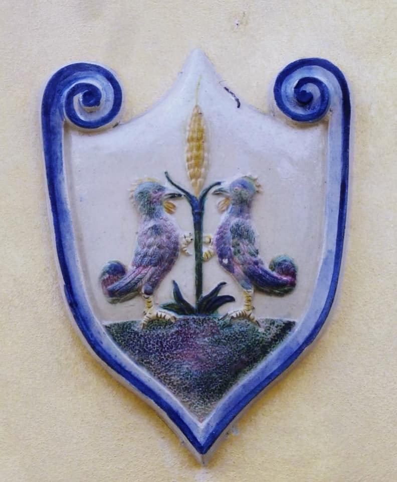 Ein Keramik-Wappen der Familie Cantagalli mit einer Ähre und zwei Hähnen.