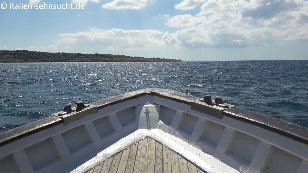 Vom Boot namens Maretta aus sieht man dessen Spitze und blickt auf Meer und Küste. Der Himmel ist hellblau, ein paar Wolken tummeln sich.