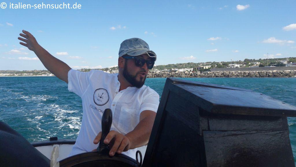 Der Kapitän Davide de Giorgi am Steuer seiner Maretta. Im Hintergrund das Meer und die Küste von Torre Vado.