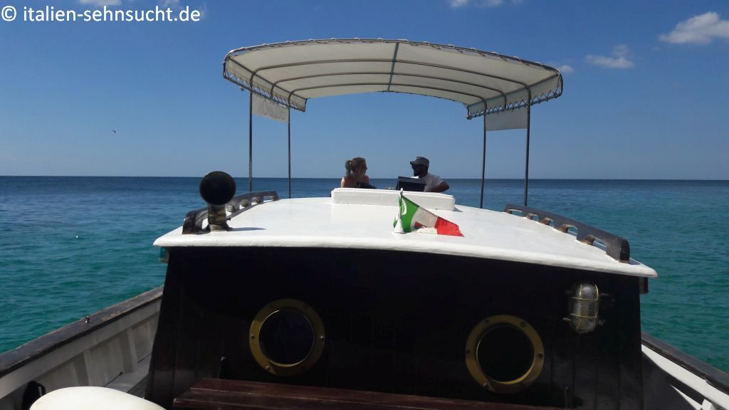 Strahlend blauer Himmel, türkisfarbenes Meer. Auf Deck Vanessa im Gespräch mit Davide de Giorgi, im Vordergrund eine italienische Flagge.