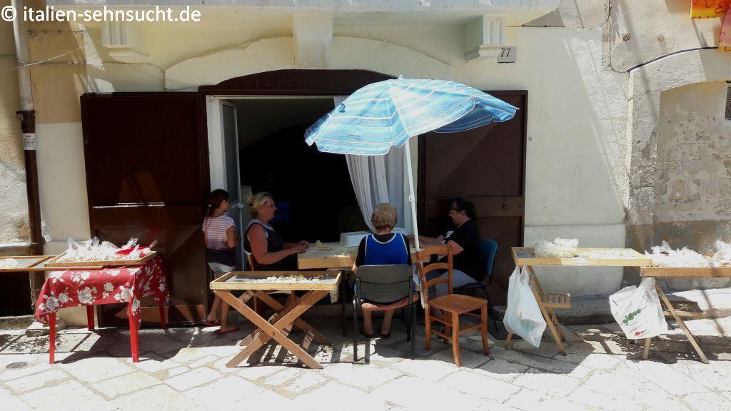 Vor ihrer Altstadtwohnung sitzen drei Frauen unter einem kleinen Sonnenschirm an einem Tisch und stellen die Nudelsorte Orecchiette her. Neben ihnen stehen Gitter mit der fertigen Pasta zur Trocknung in der Sonne. Ein Mädchen mit Ringelshirt läuft gerade in die Wohnung.