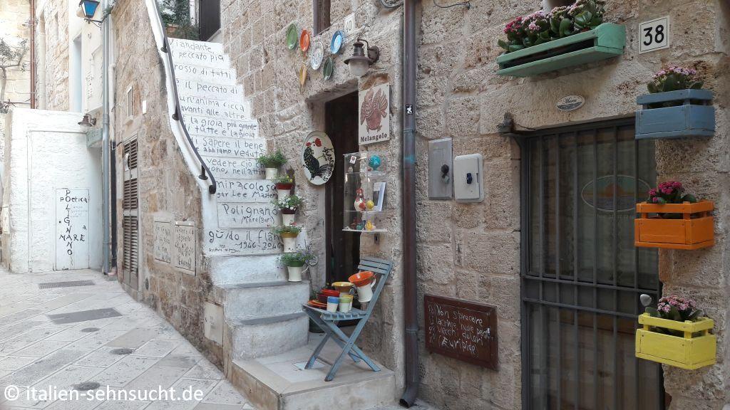 Eine schmale Treppe schmiegt sich an eine Hauswand, Guido Luporis Schriften wandern über die Stufen, Blumentöpfe und bunte Dekoobjekte zieren die Kulisse.