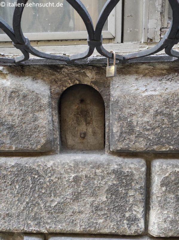 Das Weinfenster in der Via Santa Monaca, das vermutlich einst zur Cantina Mangani gehörte. Am Eisengitter des darüber liegenden Fensters hängt ein Vorhangschloss.