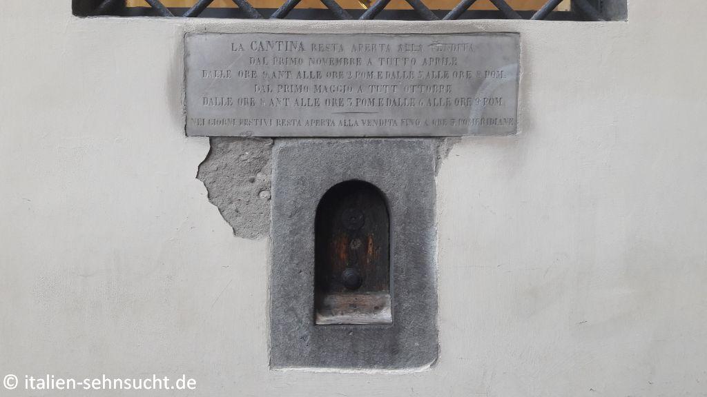 Das Weinfenster in der Via delle Belledonne mit einer Steintafel, auf der die damaligen Öffnungszeiten geschrieben stehen.