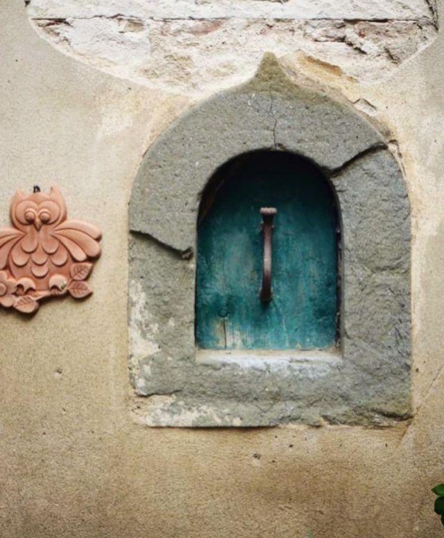 Das entzückende Weinfenster der Keramiker-Familie Cantagalli mit seinem türkisfarbenen Türchen.
