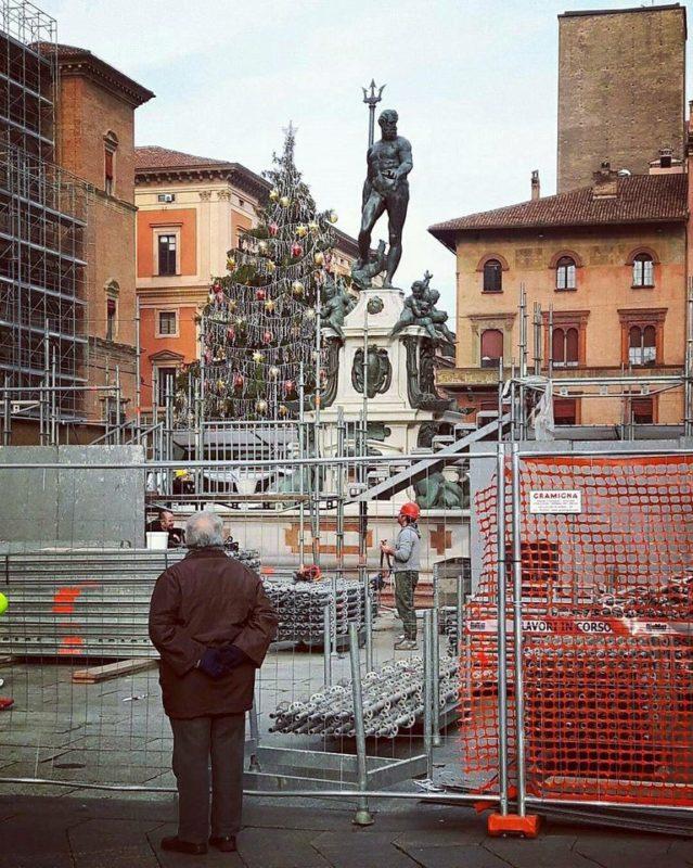 Ein älterer Herr mit verschränkten Armen hinter dem Rücken steht an einer großen Baustelle an der Piazza Nettuno in Bologna und beobachtet die Arbeiten.
