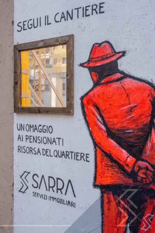Eine Baustelle von Sarra Immobilien. Eingezäunt von einer Wand mit Fenster und einem rot gezeichneten Umarell, der die Bauarbeiten durch das Fenster beobachtet.