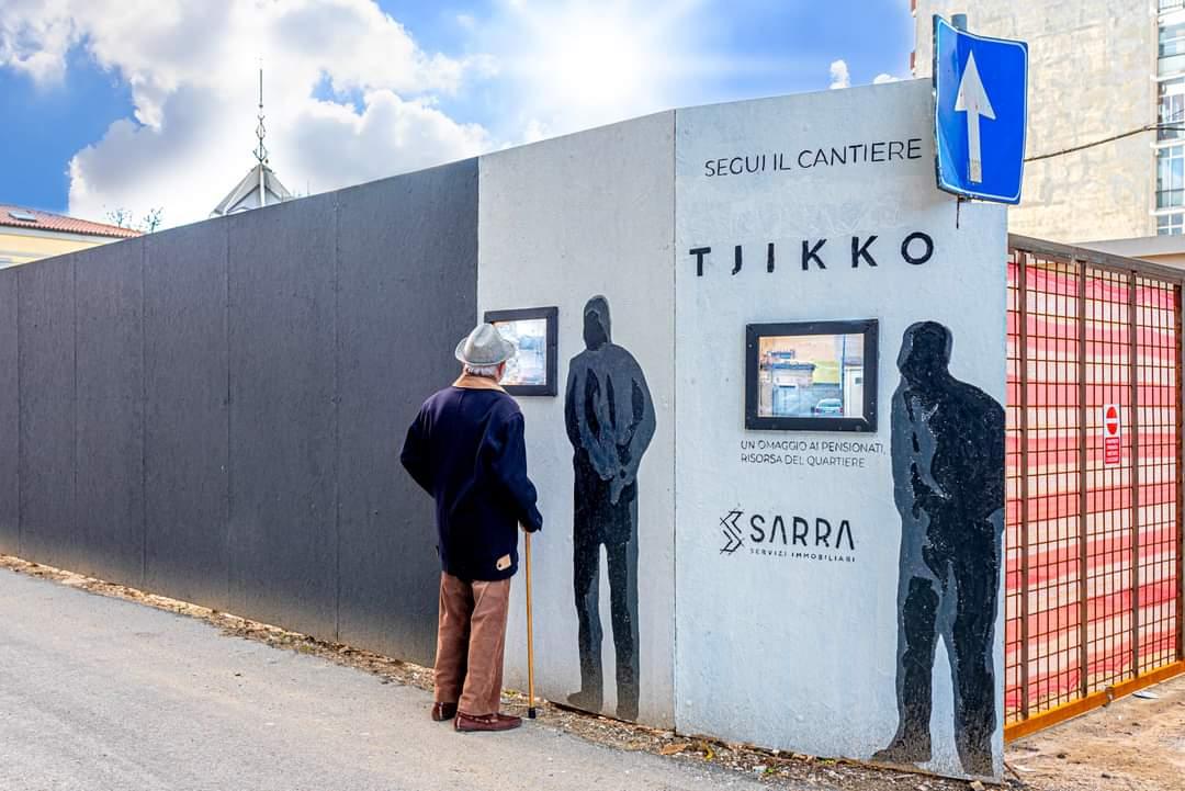 Ein Senior mit einem Stock und Hut blickt durch das Fenster an der Baustelle TJIKKO in Pescara.