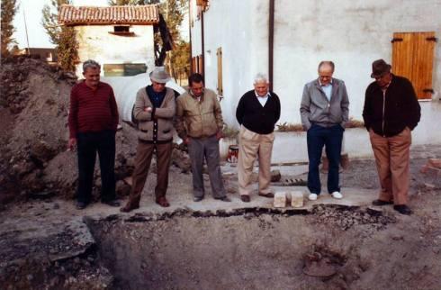 Fünf Senioren stehen am Rande einer Baugrube und sehen hinein. Einer in der berühmten Pose des Umarell mit den Händen auf dem Rücken, drei mit den Händen in den Hosentaschen, einer rauchend.